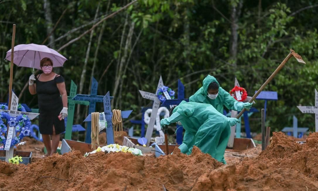 Coveiros trabalham para enterrar vítimas confirmadas e suspeitas do novo coronavírus, em Manaus Foto: MICHAEL DANTAS / AFP