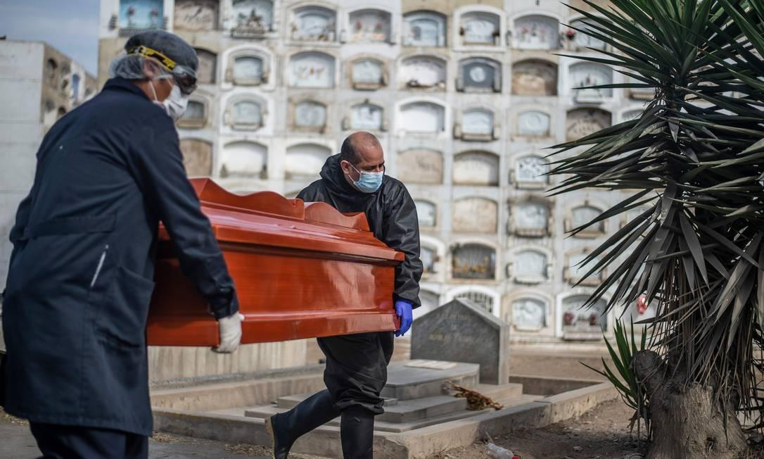 Trabalhadores carregam caixão com vítima da Covid-19 para cremação em Lima Foto: ERNESTO BENAVIDES / AFP