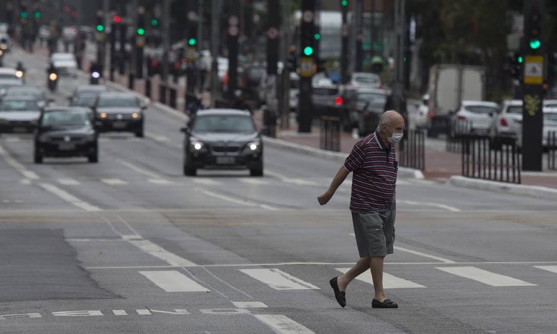 Um homem usa máscara enquanto caminha por rua de São Paulo. Multas, por enquanto, estão previstas para estabelecimentos comerciais que que não respeitarem a determinação Foto: Edilson Dantas / Agência O Globo