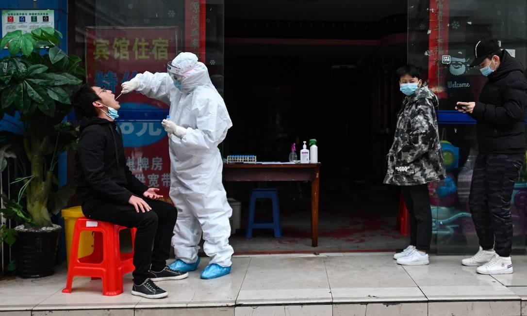 Profissional de saúde coleta amostra para testes de Covid-19 em Wuhan, na China Foto: HECTOR RETAMAL / AFP
