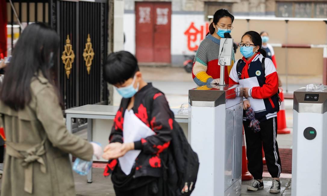 Escolas também estão sendo reabertas na China. Na imagem, a temperatura de uma criança é checada antes dela entrar em um colégio do país Foto: AFP