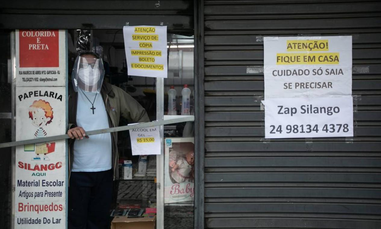 Comerciante em Sapucaia mantém loja funcionando com porta aberta pela metade e sem clientes em seu interior Foto: Brenno Carvalho / Agência O Globo