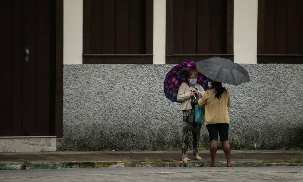 Duas mulheres conversam usando máscaras, mas manter distância segura em uma rua de Sapucaia Foto: Brenno Carvalho / Agência O Globo