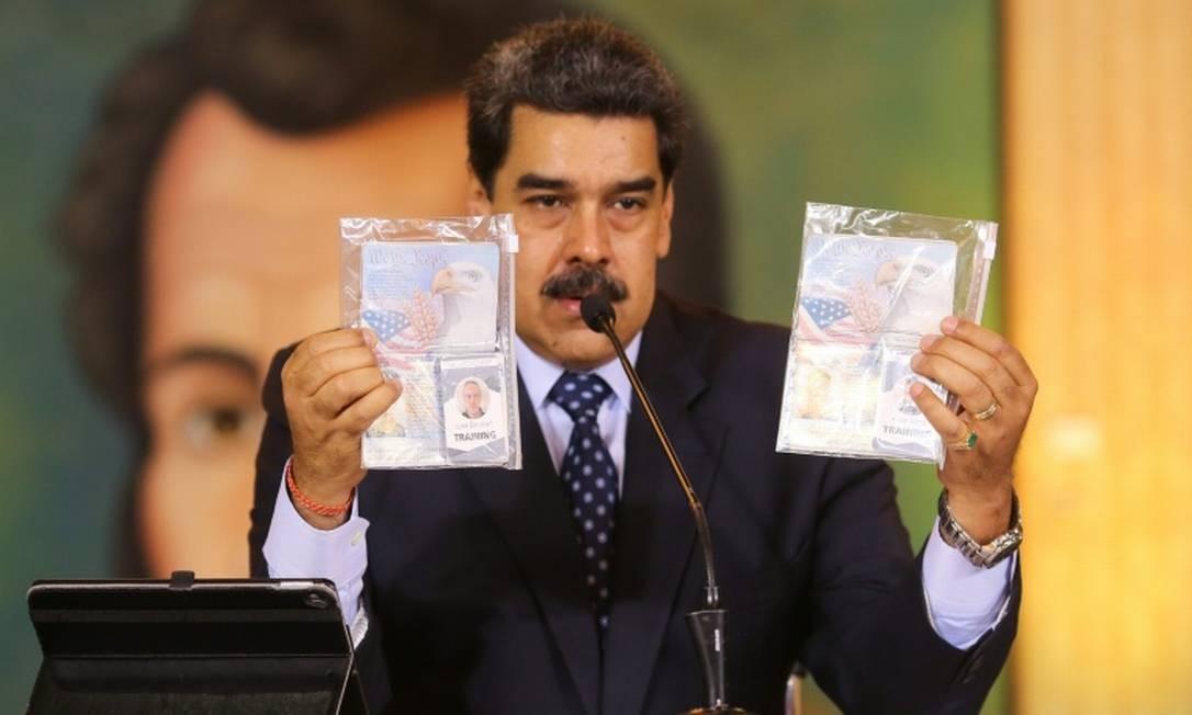 O presidente venezuelano, Nicolás Maduro, mostra os passaprotes dos dois americanos presos pelas forças de segurança da Venezuela Foto: AFP / Marcelo Garcia