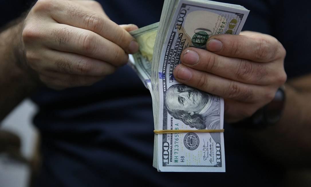 Investimento em dólar: segurança contra crise. Foto: AHMAD AL-RUBAYE / AFP