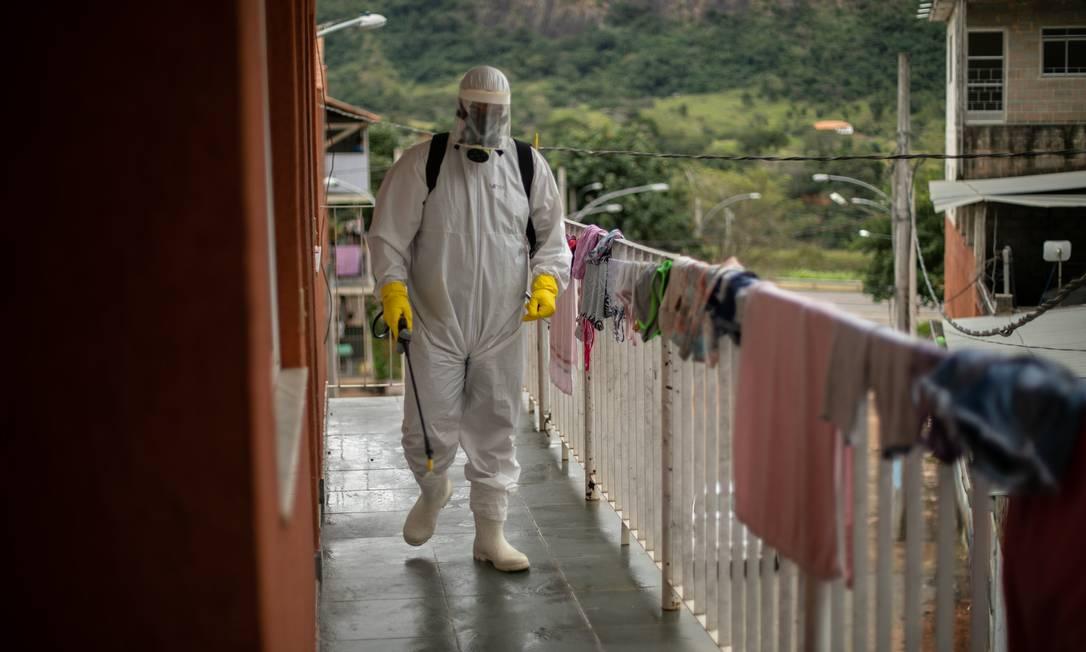 Funcionário da Vigilância Sanitária de Sapucaia faz limpeza em condomínio onde houve caso suspeito de Covid-19: cidade está na rota da doença que se espalha pelo Estado do Rio Foto: Brenno Carvalho / Agência O Globo