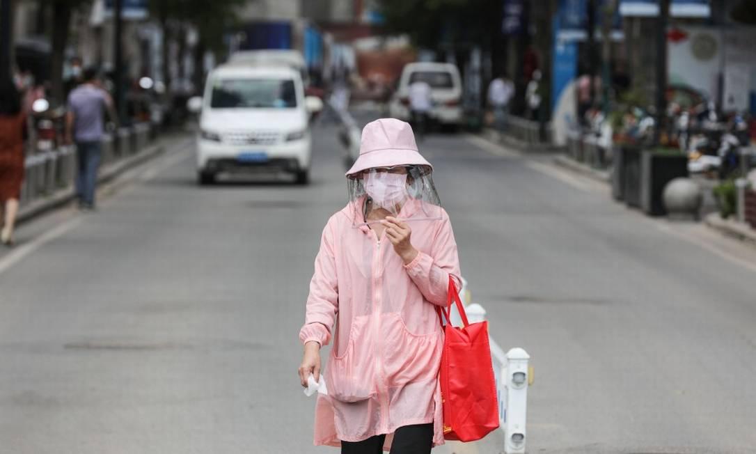Mulher usa máscara para andar na rua em Wuhan, na província central de Hubei Foto: STR / AFP