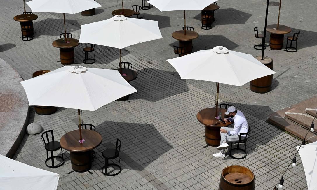 Homem desfruta de um lanche numa mesa ao ar livre, em um café em Kiev, nesta segunda-feira. A Ucrânia começou a suspender parcialmente algumas restrições adotadas para conter o surto de Covid-19. Cafés ao ar livre, salões de beleza, clínicas dentárias, parques e praças foram reabertos ao público Foto: SERGEI SUPINSKY / AFP