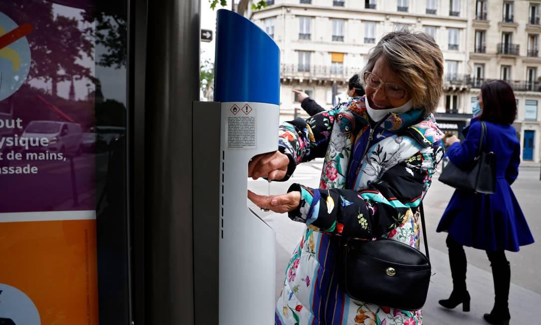 Mulher desinfeta as mãos com álcool em gel em uma parada de ônibus em Paris Foto: THOMAS COEX / AFP