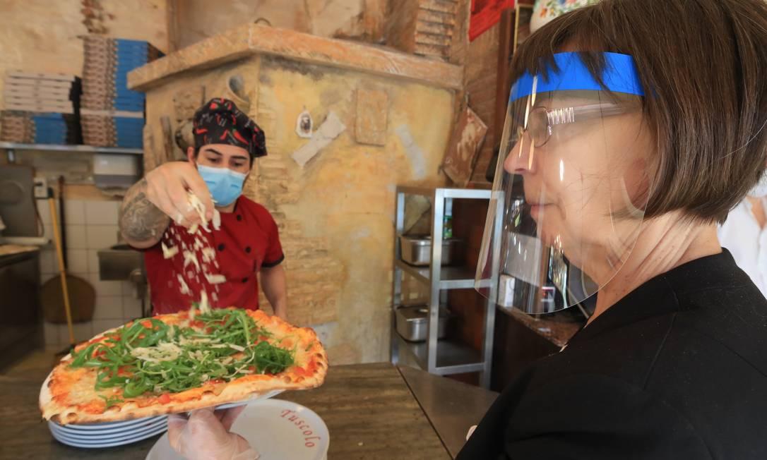 O pizzaiolo Carmelo la Ciura e a garçonete Dorina Zettler servem clientes no restaurante Tuscolo, que reabriu nesta segunda-feira, após semanas de fechamento devido ao surto do novo coronavírus, em Bonn, Alemanha Foto: WOLFGANG RATTAY / REUTERS