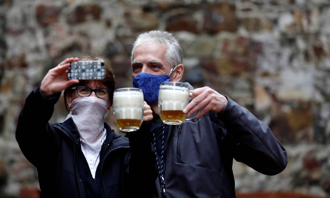 Casal posa para selfie com suas cervejas em área ao ar livre de um pub em Praga, capital da República Tcheca, que autorizou a reabertura de restaurantes com áreas externas em meio ao surto de doença por coronavírus, a partir desta segunda-feira Foto: DAVID W CERNY / REUTERS