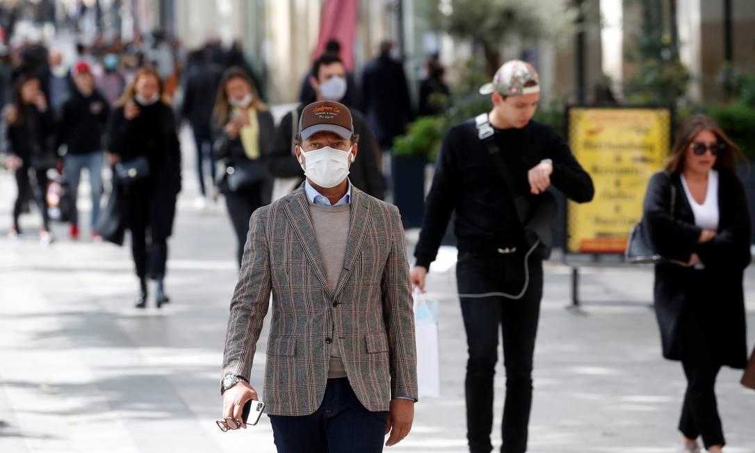 Pessoas usam máscaras em avenida de Paris. França começa a relaxar medidas de restrição e isolamento social Foto: Gonzalo Fuentes/Reuters