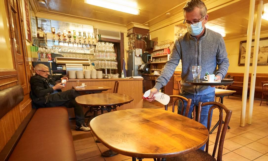 Garçom desinfeta mesa depois de cliente deixá-la no Cafe du Soleil, em Genebra, na Suíça, que também começou a flexiblizar as regras do lockdown Foto: DENIS BALIBOUSE / REUTERS