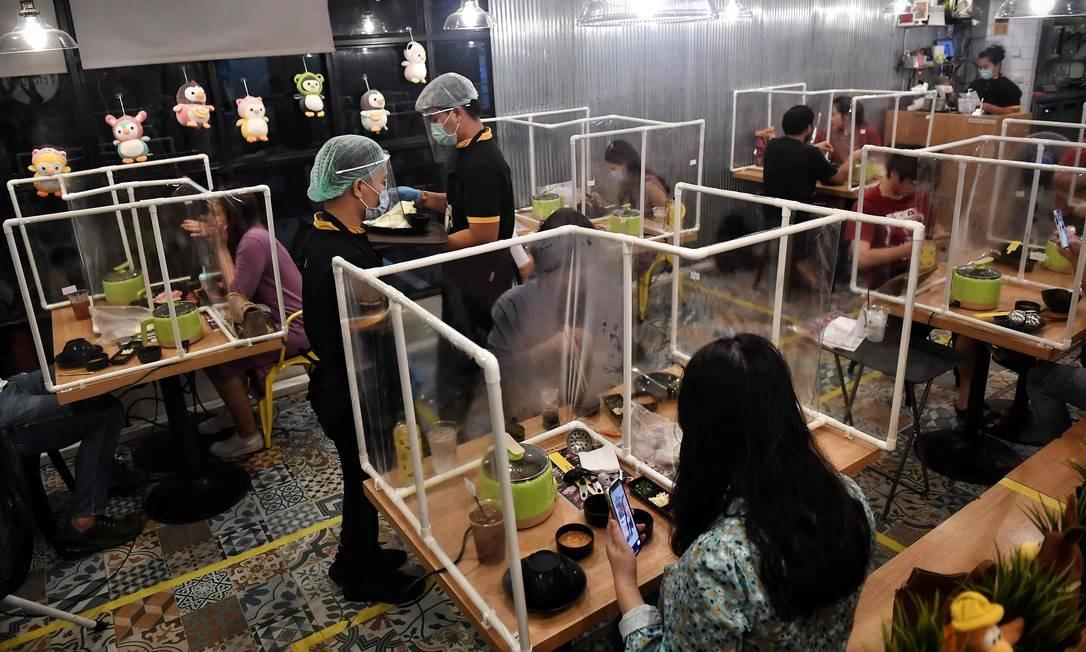 Clientes comem entre as divisórias plásticas, criadas para conter qualquer disseminação do coronavírus no restaurante Penguin Eat Shabu, em Bangkok Foto: LILLIAN SUWANRUMPHA / AFP