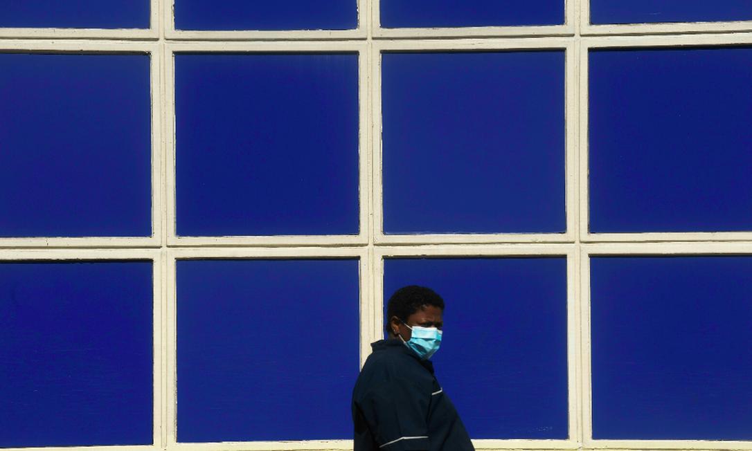 Pedestre com máscara em Caxias. Baixada, Região Metropolitana adotam medidas mais restritivas Foto: Antonio Scorza / Agência O GLOBO