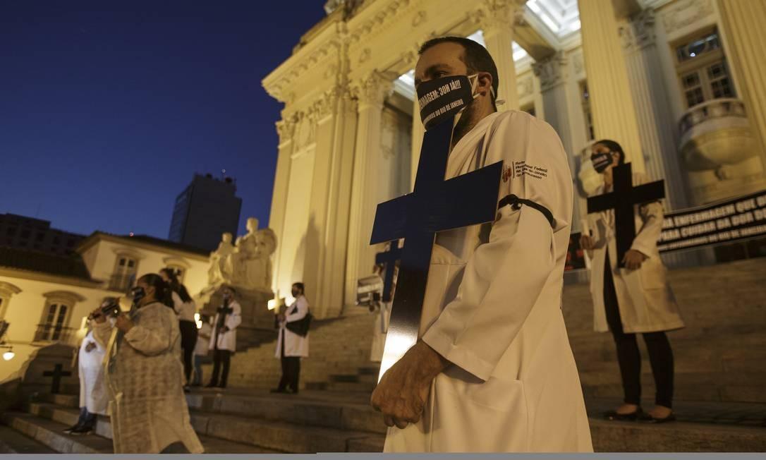 De jaleco branco e máscaras pretas, manifestantes carregavam cruzes e velas em homenagem aos enfermeiros mortos pela Covid-19 Foto: Alexandre Cassiano / Agência O Globo