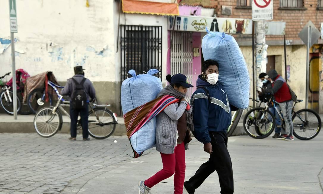 Casal leva mercadorias em rua de El Alto, na Bolívia, no dia 30 de abril Foto: AIZAR RALDES / AFP