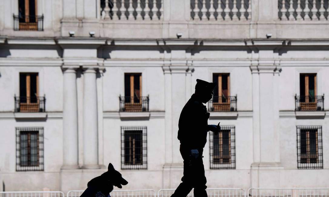 Um policial e seu cachorro caminham do lado de fora do palácio presidencial do Chile, em Santiago, no dia em que o governo anunciou um confinamento total na capital Foto: Martin Bernetti / AFP