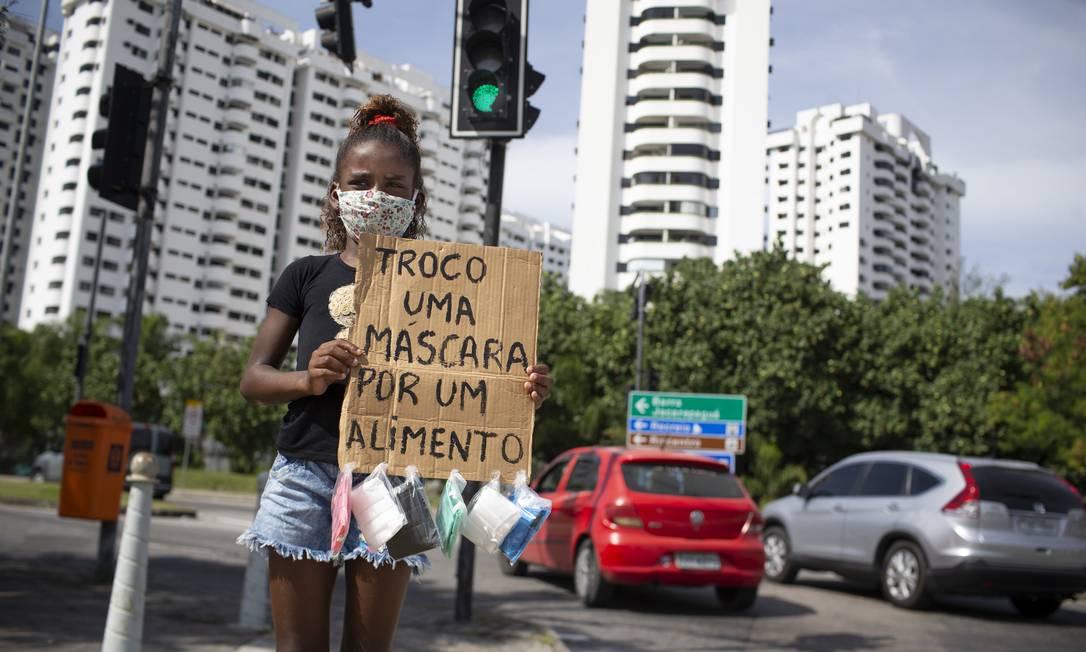 A menina Ana Júlia, de 9 anos, com cartaz em que oferece máscara em troca de alimentos em sinal do Recreio Foto: Márcia Foletto / Agência O Globo