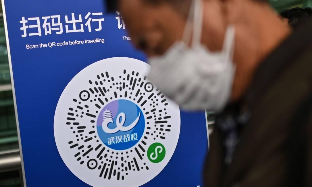Passageiro usando uma máscara facial passa por um código QR de saúde da cidade de Wuhan, a ser digitalizado antes de entrar no Aeroporto de Tianhe. Na China, aplicativos de rastreamento do coronavírus estão em toda parte para controlar a propagação da Covid-19 Foto: HECTOR RETAMAL / AFP
