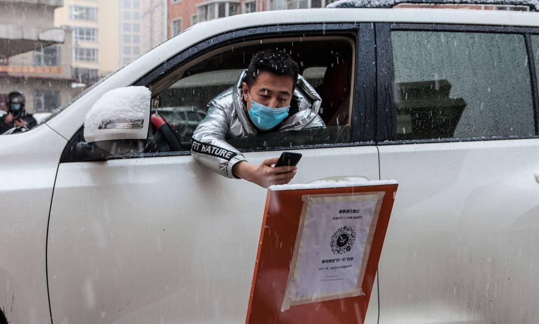 Motorista escaneia um código QR para registrar informações antes de entrar em uma comunidade durante uma nevasca na cidade fronteiriça de Suifenhe, na província de Heilongjiang, no nordeste da China. O aplicativo criado pelo governo é baseado nos dados de geolocalização das operadoras e analisa os movimentos do usuário nos 14 dias anteriores, em particular para descobrir se ele esteve em uma área de risco, ou se esbarrou com alguém com COVID-19 Foto: STR / AFP