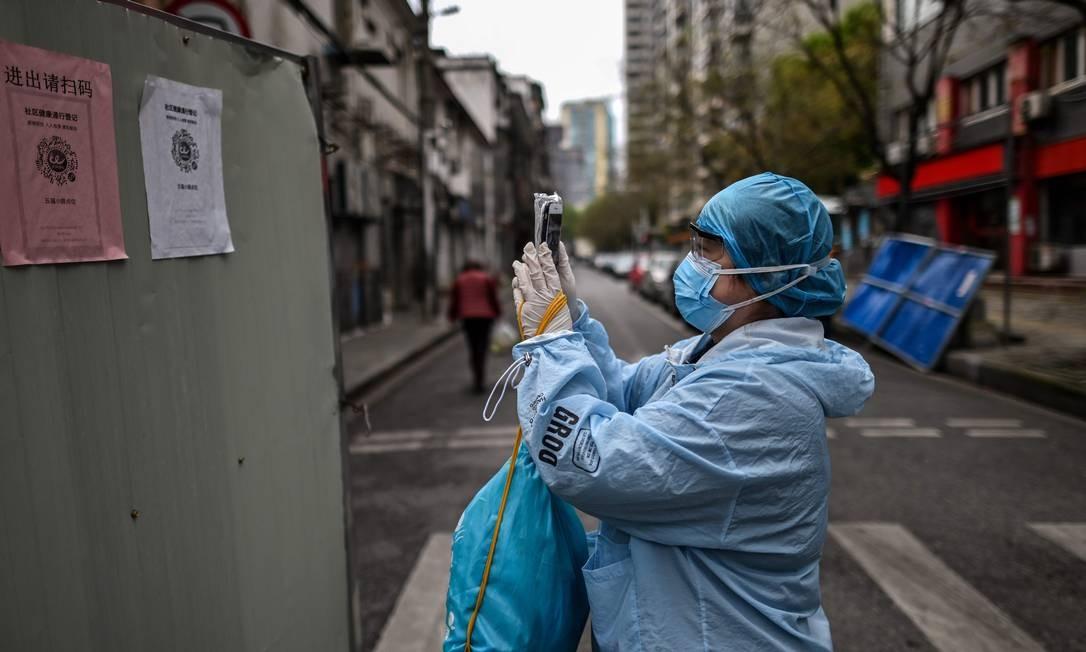 Uma mulher vestindo um traje de proteção e máscara facial em meio à pandemia de Covid-19 usa seu telefone para escanear um código de saúde da cidade de Wuhan, epicentro inicial da pandemia, antes de entrar em um complexo residencial. Na China, 4.633 mortes por coronavírus foram registradas oficialmente desde o início da pandemia Foto: HECTOR RETAMAL / AFP