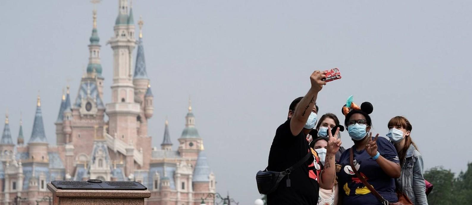 Usando máscaras, visitantes tiram uma selfie em frente ao Castelo dos Contos de Fadas, na Shanghai Disneyland Foto: Aly Song / Reuters