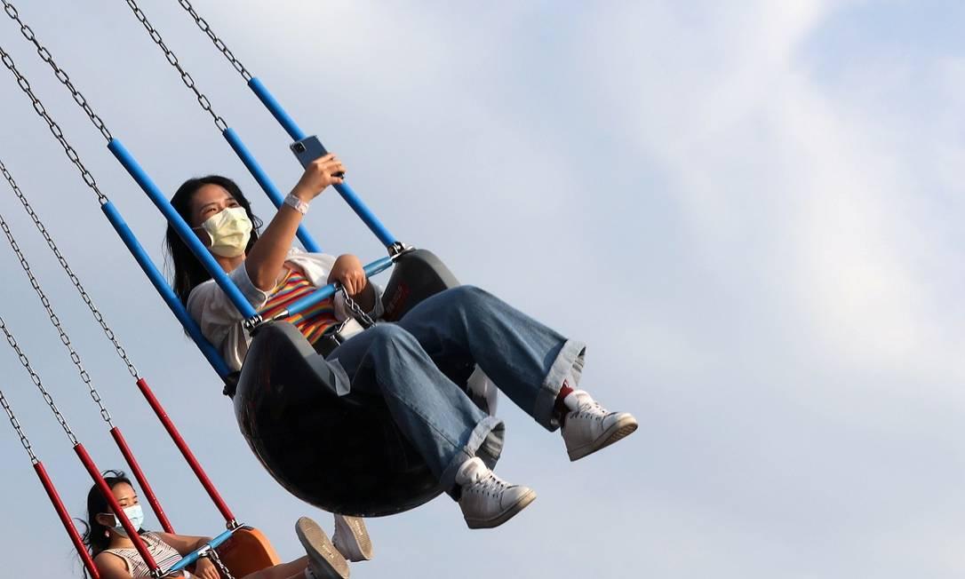 Uma mulher, usando máscara, aproveita um dos brinquedos do Taipei Children's Amusement Park, em Taipei, na ilha de Taiwan Foto: Ann Wang / Reuters