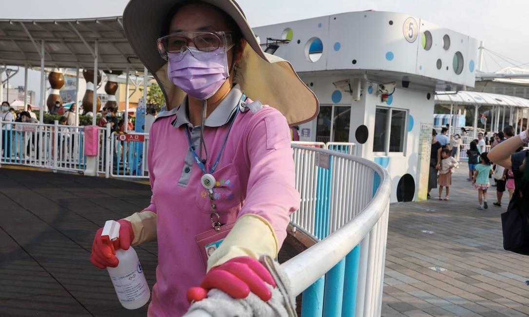 Funcionária, paramentada com máscara e luvas, limpa uma atração do Taipei Children's Amusement Park, em Taiwan Foto: Ann Wang / Reuters