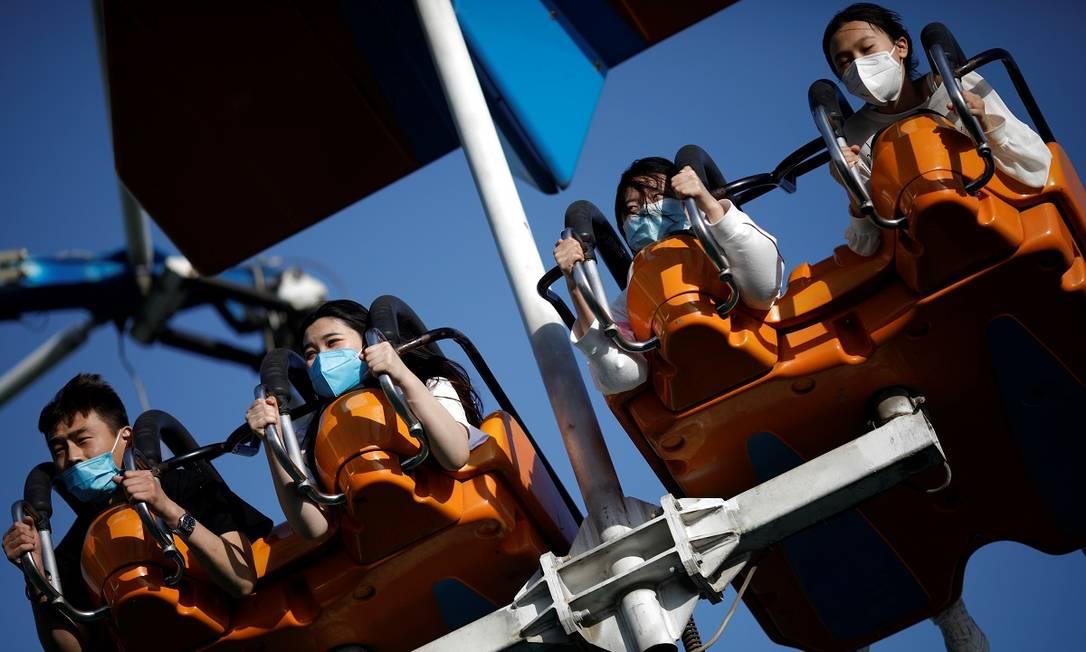 Frequentadores usando máscara num brinquedo do parque Happy Valley, em Pequim Foto: Carlos Garcia Rawlins / Reuters