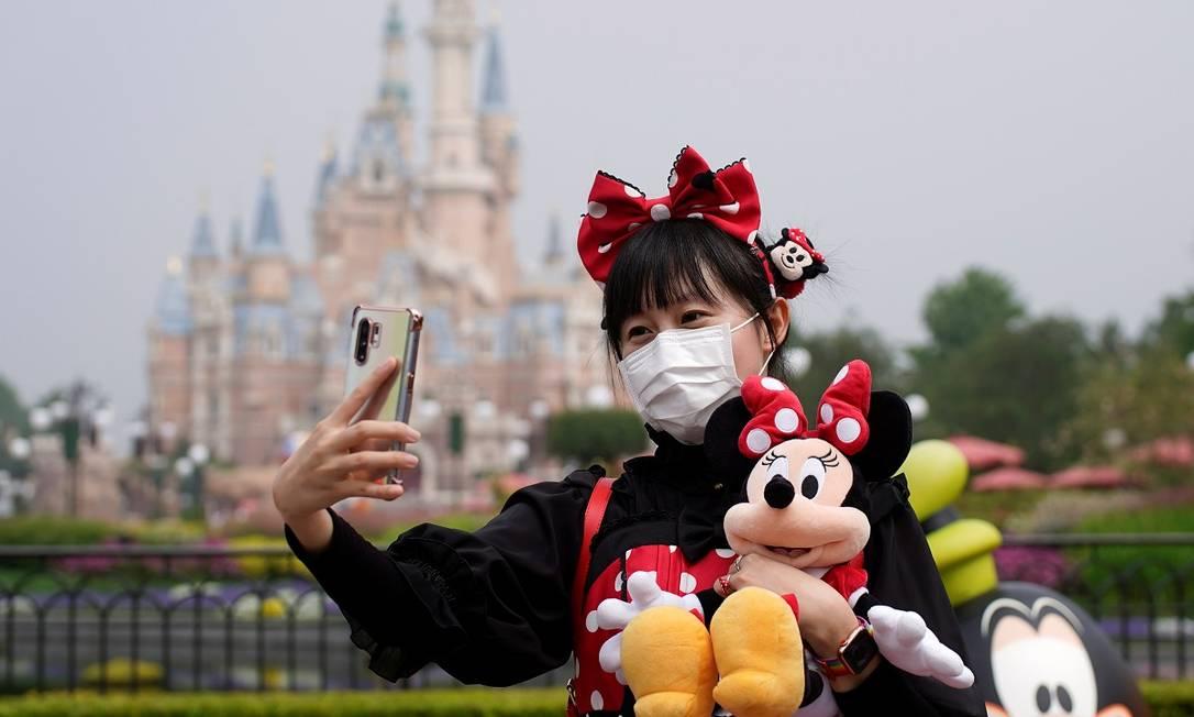Máscara e orelhas de Mickey: traje completo na Disneyland Shanghai em tempos de novo coronavírus Foto: Aly Song / Reuters