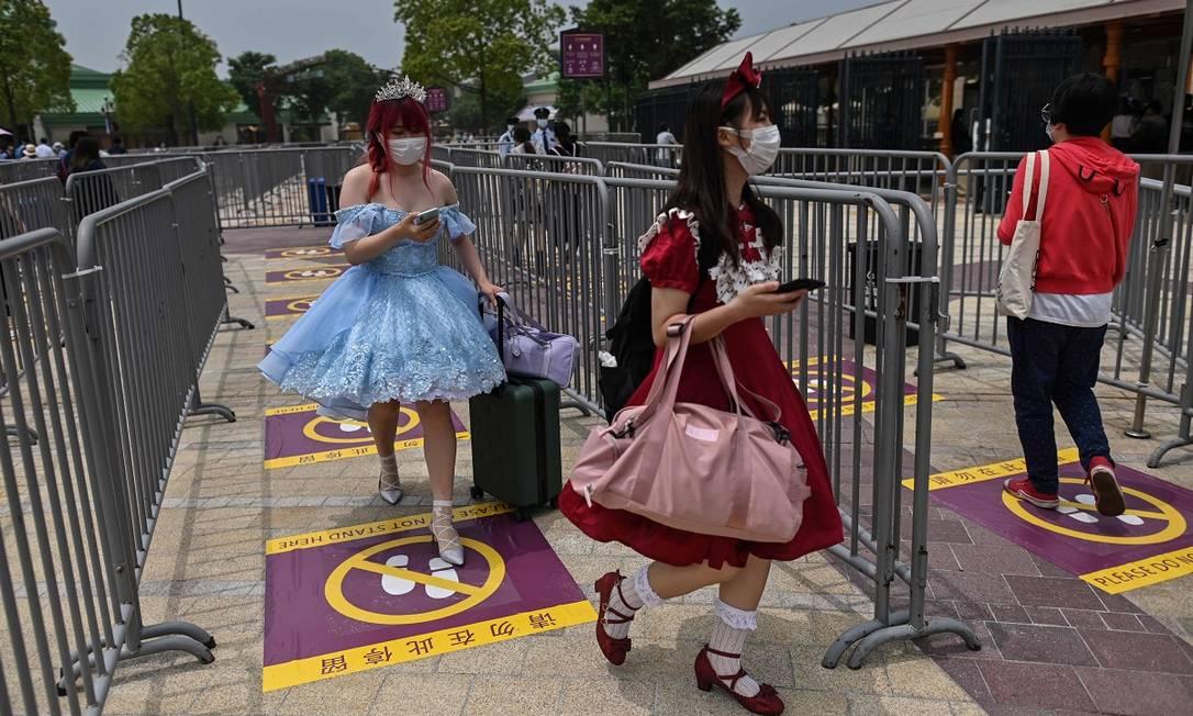 Fila com marcações no chão para delimitar a distância de 1,5 metro entre as pessoas na Disneyland de Xangai Foto: Hector Retamal / AFP