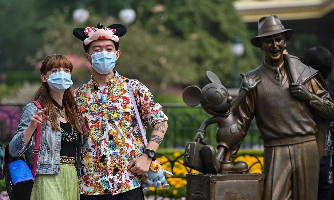 Casal de máscara na Disneyland de Xangai Foto: Hector Retamal / AFP