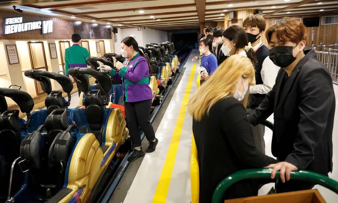 Usando máscaras, visitantes esperam para embarcar na montanha-russa de um parque em Seul, na Coreia do Sul, enquanto uma funcionária limpa o carrinho Foto: Kim Hong-Ji / Reuters