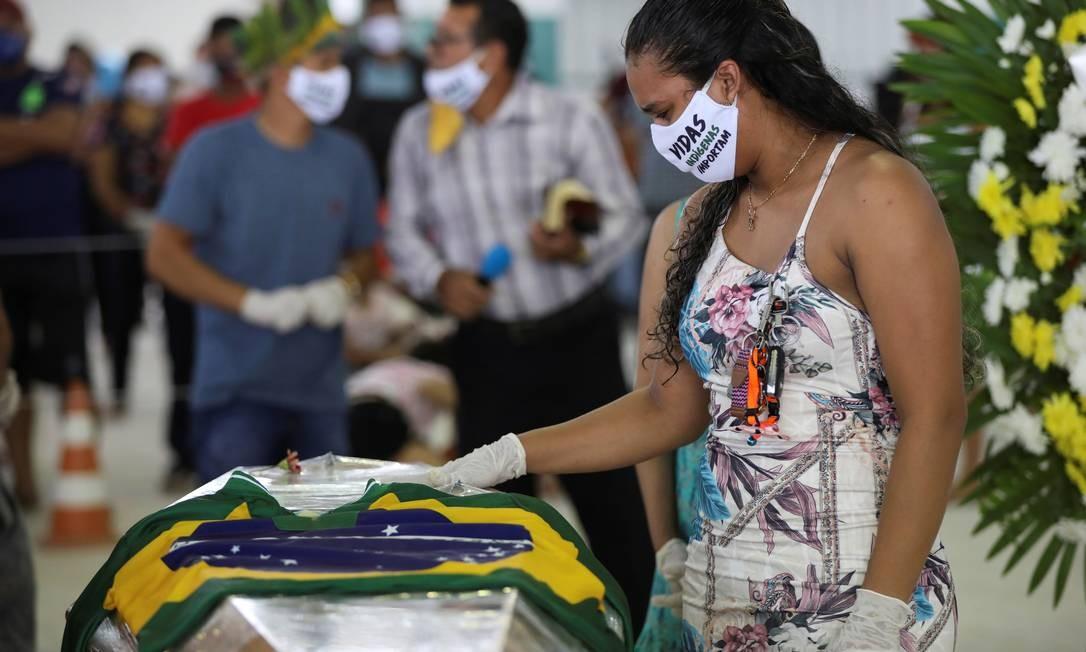 """Mulher indígena, usando uma máscara facial com a inscrição """"Vidas indígenas importam"""", participa do funeral do chefe Messias Kokama, 53 anos, do Parque das Tribos, que morreu devido à COVID-19, em Manaus, no Brasil Foto: BRUNO KELLY / REUTERS"""