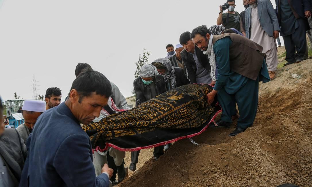 Homens carregam corpo de uma das pessoas mortas durante atentado em uma maternindade em Cubal, no Afeganistão Foto: AFP