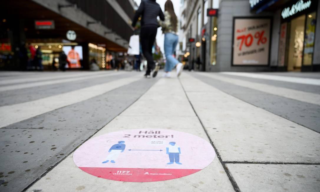 Adesivo em rua comercial de Estocolmo pede que as pessoas mantenham distância de pelo menos dois metros em relação a outros transeuntes Foto: HENRIK MONTGOMERY / AFP