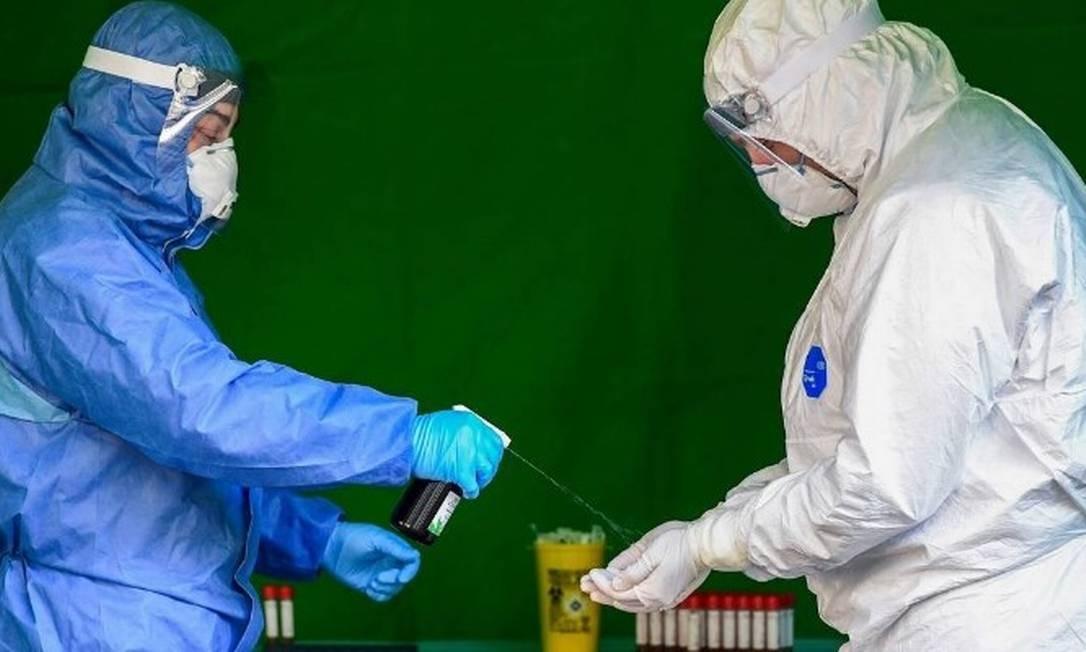 Profissionais de saúde desinfetam as luvas enquanto realizam testes para diagnosticar o coronavírus Foto: MIGUEL MEDINA/AFP