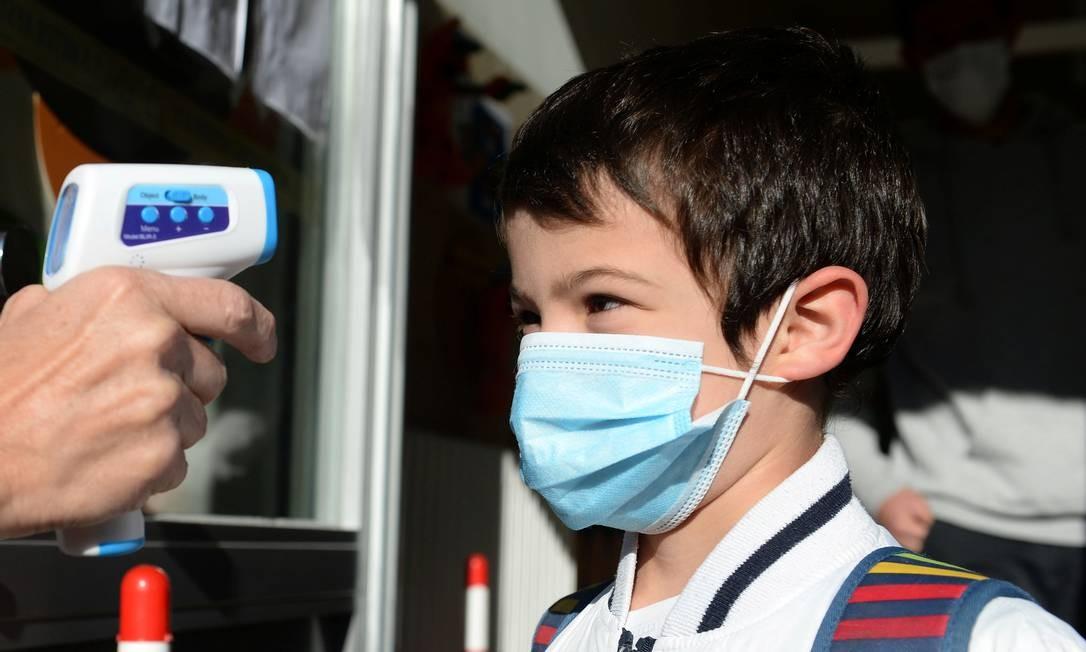 Professora mede temperatura de criança antes de entrar na escola, em Bruxelas, na Bélgica Foto: JOHANNA GERON / REUTERS