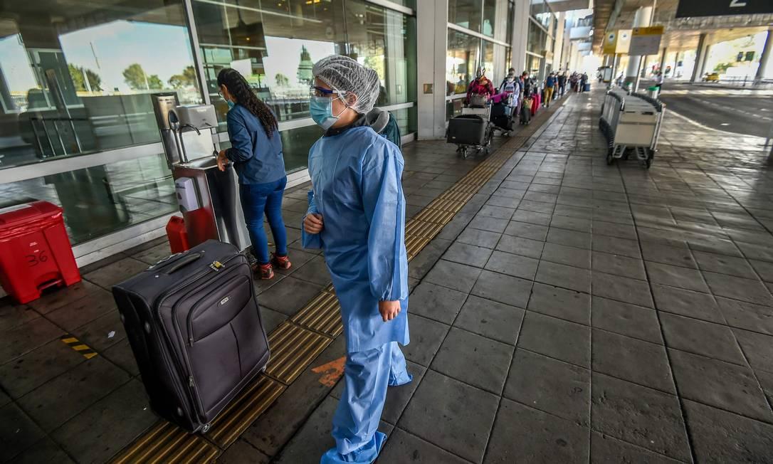 Profissional de saúde antes de embarcar em um voo humanitário para Buenos Aires no aeroporto de Bogotá em 14 de maio de 2020, em meio à nova pandemia de coronavírus. Foto: JUAN BARRETO / AFP