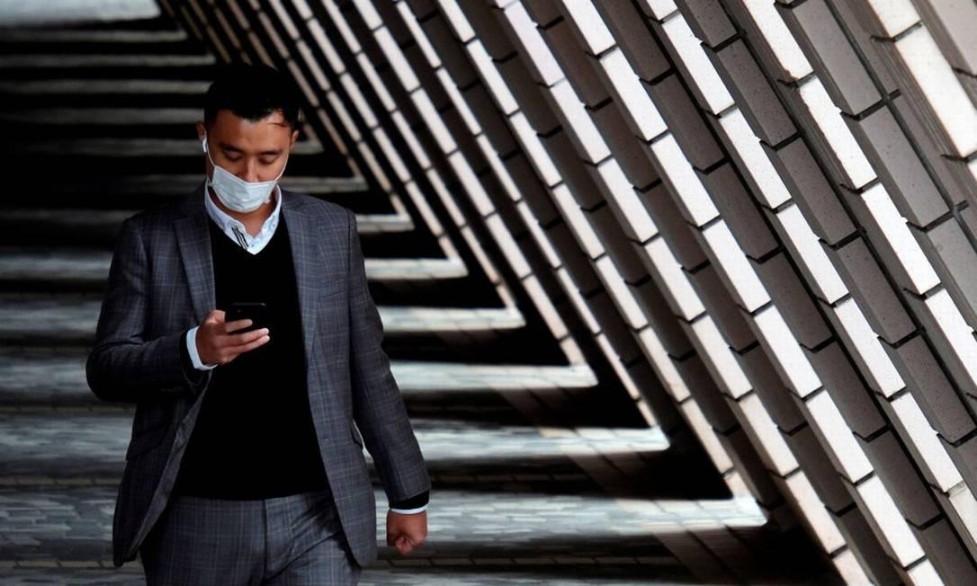 Homem usando máscara de proteção anda pelo distrito de Tsim Sha Tsui, em Hong Kong Foto: Tyrone Siu / REUTERS