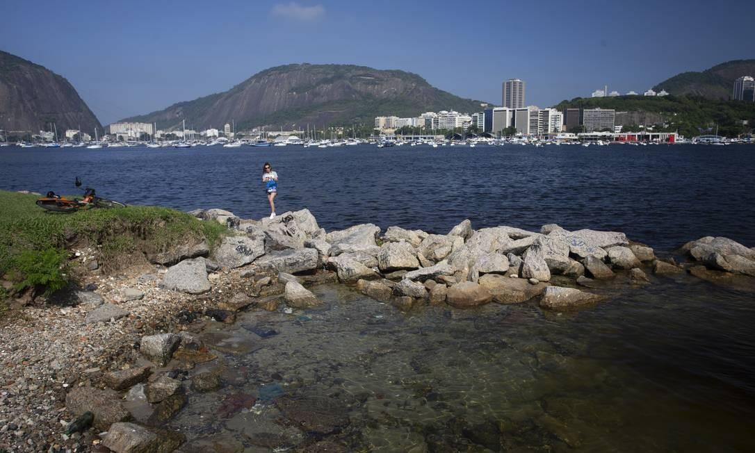 Uma mulher fotografa a Praia de Botafogo em dia de águas claras, o que é raro Foto: Márcia Foletto / Agência O Globo