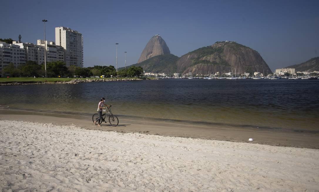 Mulher caminha na Praia de Botafogo, admirando a rara condição das águas Foto: Márcia Foletto / Agência O Globo