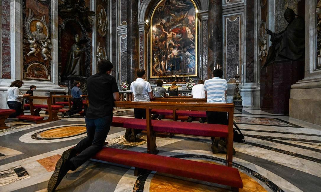As pessoas rezam junto ao túmulo do falecido papa João Paulo II no 100º aniversário de seu nascimento, na Basílica de São Pedro Foto: VINCENZO PINTO / AFP