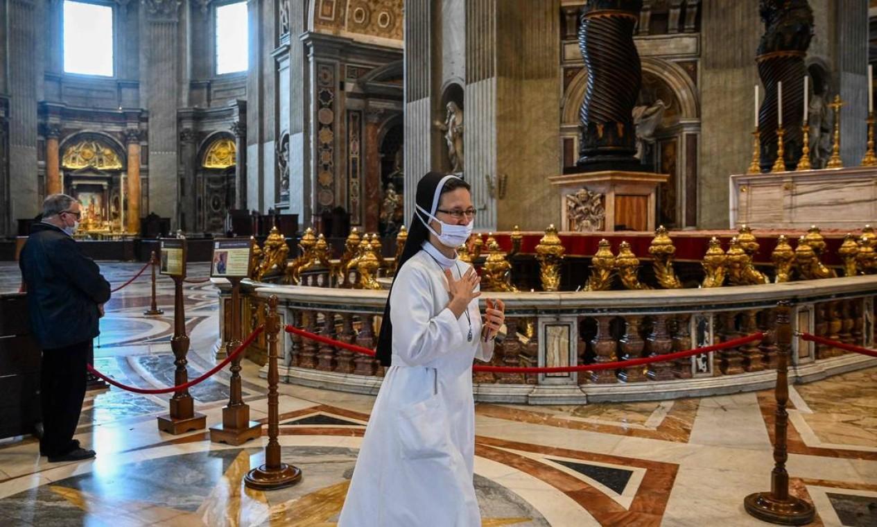Uma freira faz o sinal da cruz enquanto visita a Basílica de São Pedro Foto: VINCENZO PINTO / AFP