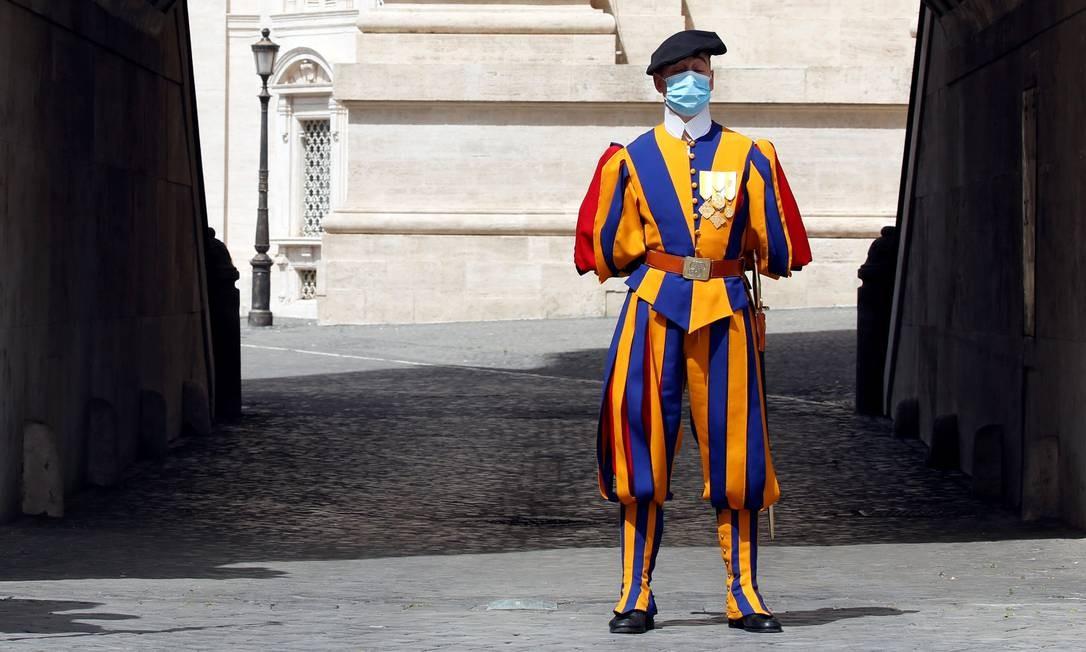 Um membro da Guarda Suíça vigia a Basílica de São Pedro, enquanto o Vaticano facilita as medidas adotadas durante o surto de coronavírus, no Vaticano Foto: REMO CASILLI / REUTERS