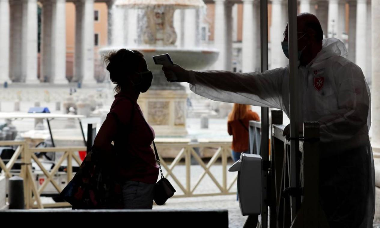 Uma mulher tem sua temperatura verificada antes de entrar na Basílica de São Pedro Foto: REMO CASILLI / REUTERS