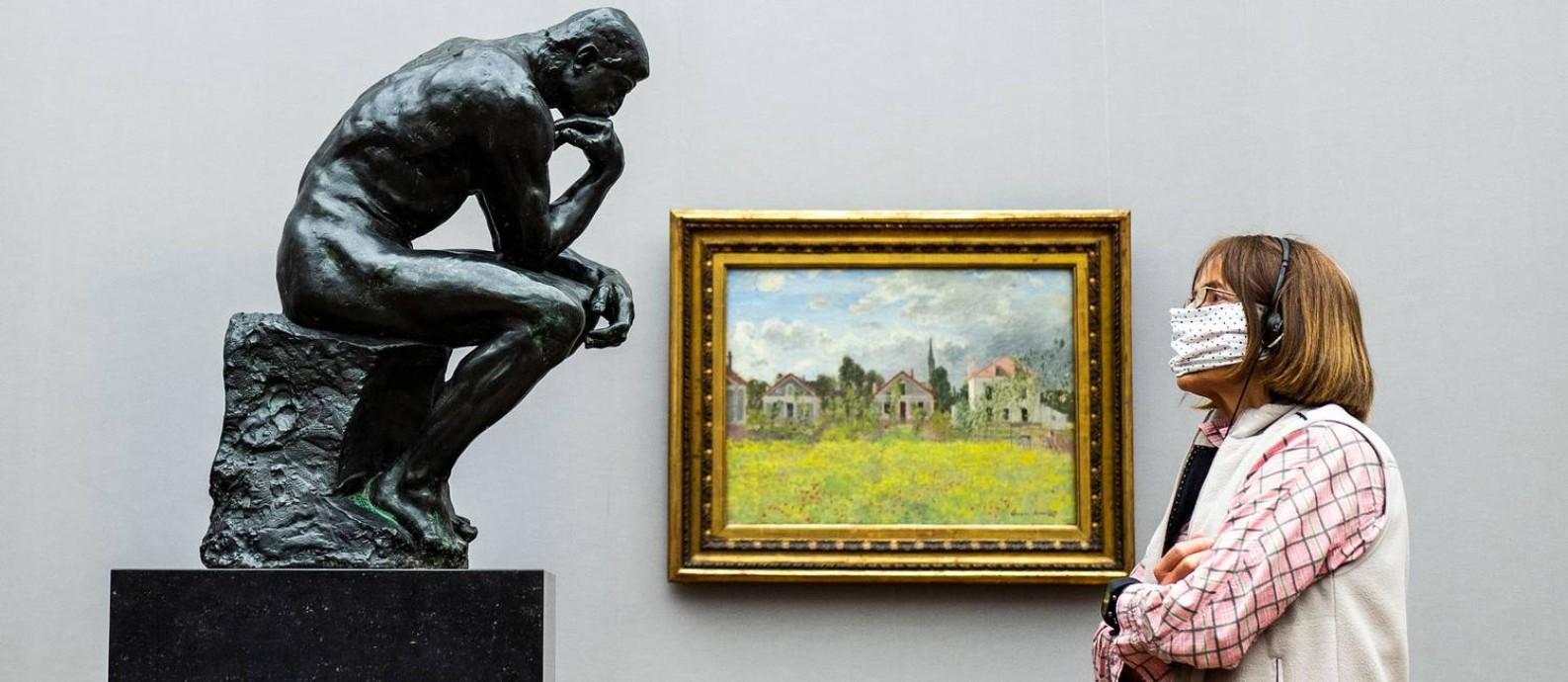 Uma vistante de máscara olha a uma versão em mármore e bronze de 'O pensador', assinada por Auguste Rodin, na Alte Nationalgalerie de Berlim, reaberta no dia 12 Foto: JOHN MACDOUGALL / AFP