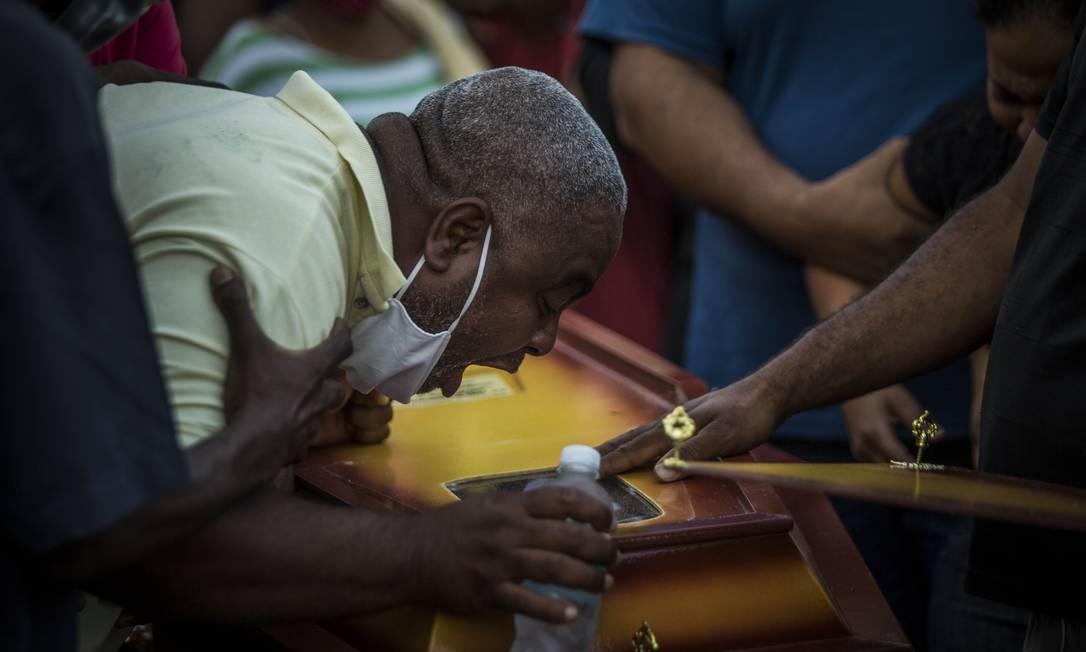 O pai de João, Neilton, debruçado sobre o caixão do filho Foto: Guito Moreto / Agência O Globo