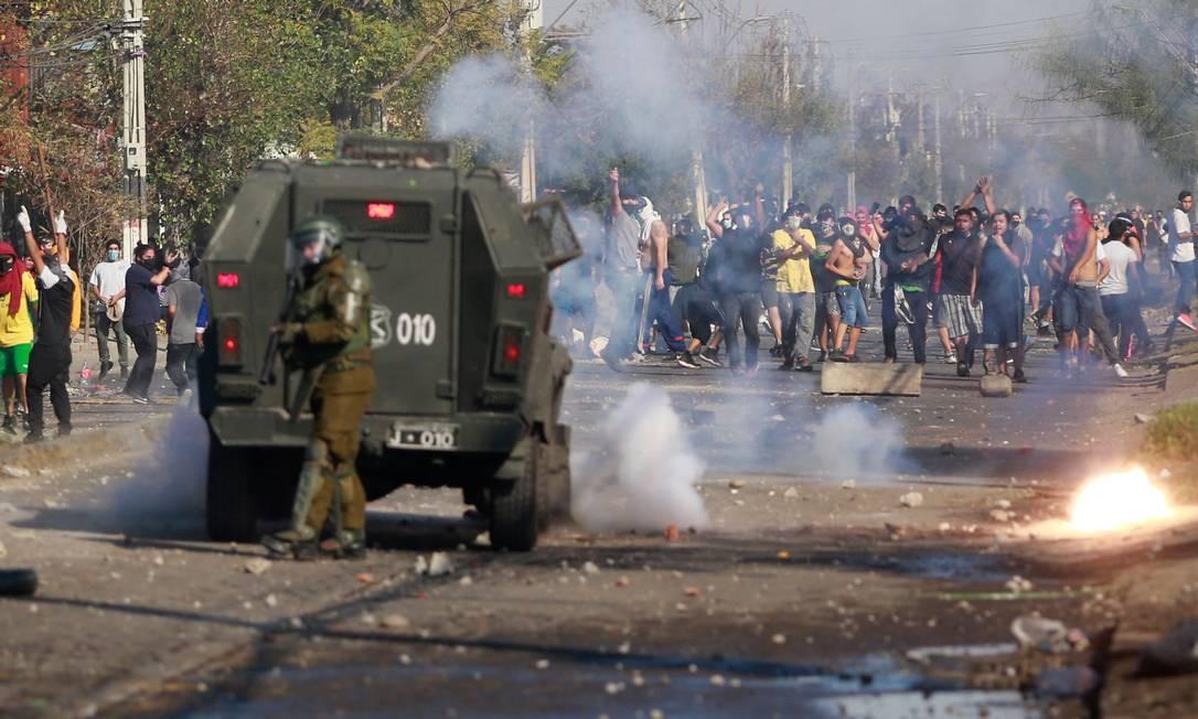 Um policial se protege atrás de um carro blindado enquanto manifestantes atiram pedras contra as forças de segurança. Confrontos entre moradores e policiais eclodiram no bairro pobre de El Bosque, em Santiago Foto: PABLO ROJAS / AFP